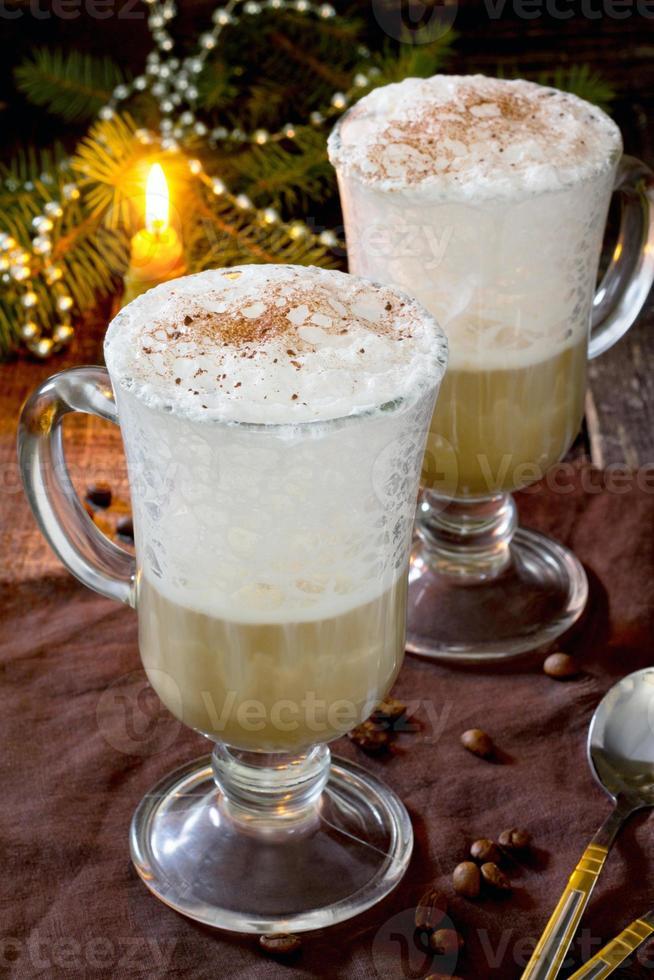 cappuccino med ett dekorerat julgran på ett träbord foto