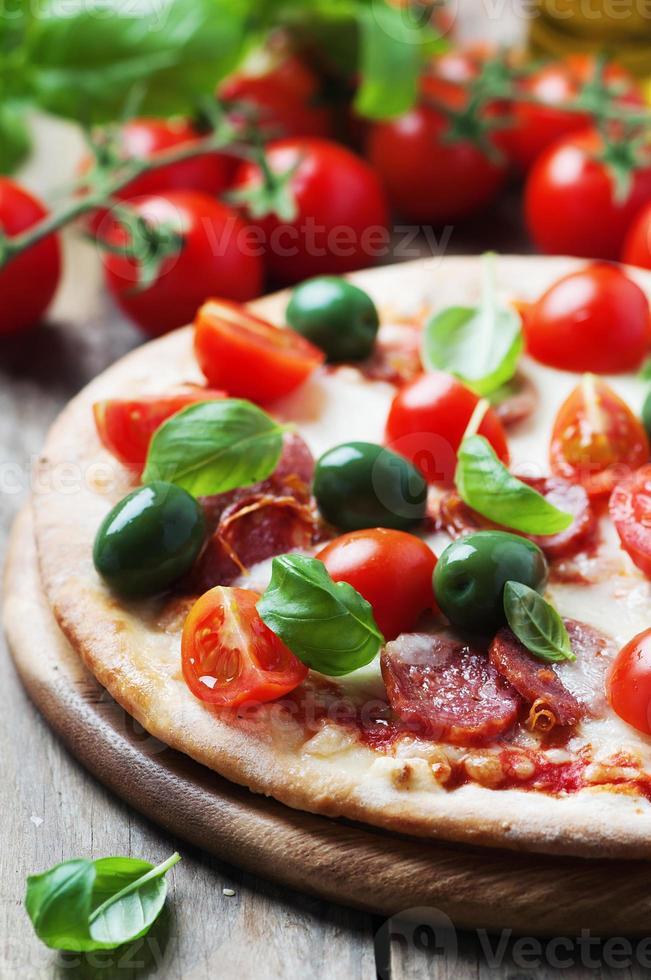 italiensk varm pizza med salami, oliv och tomat foto