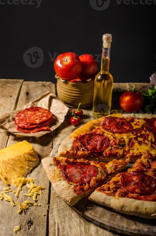 rustik salamipizza med cheddarost och chorizo foto