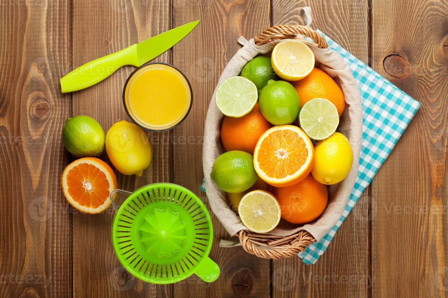 citrusfrukter och glas juice. apelsiner, limefrukter och citroner foto