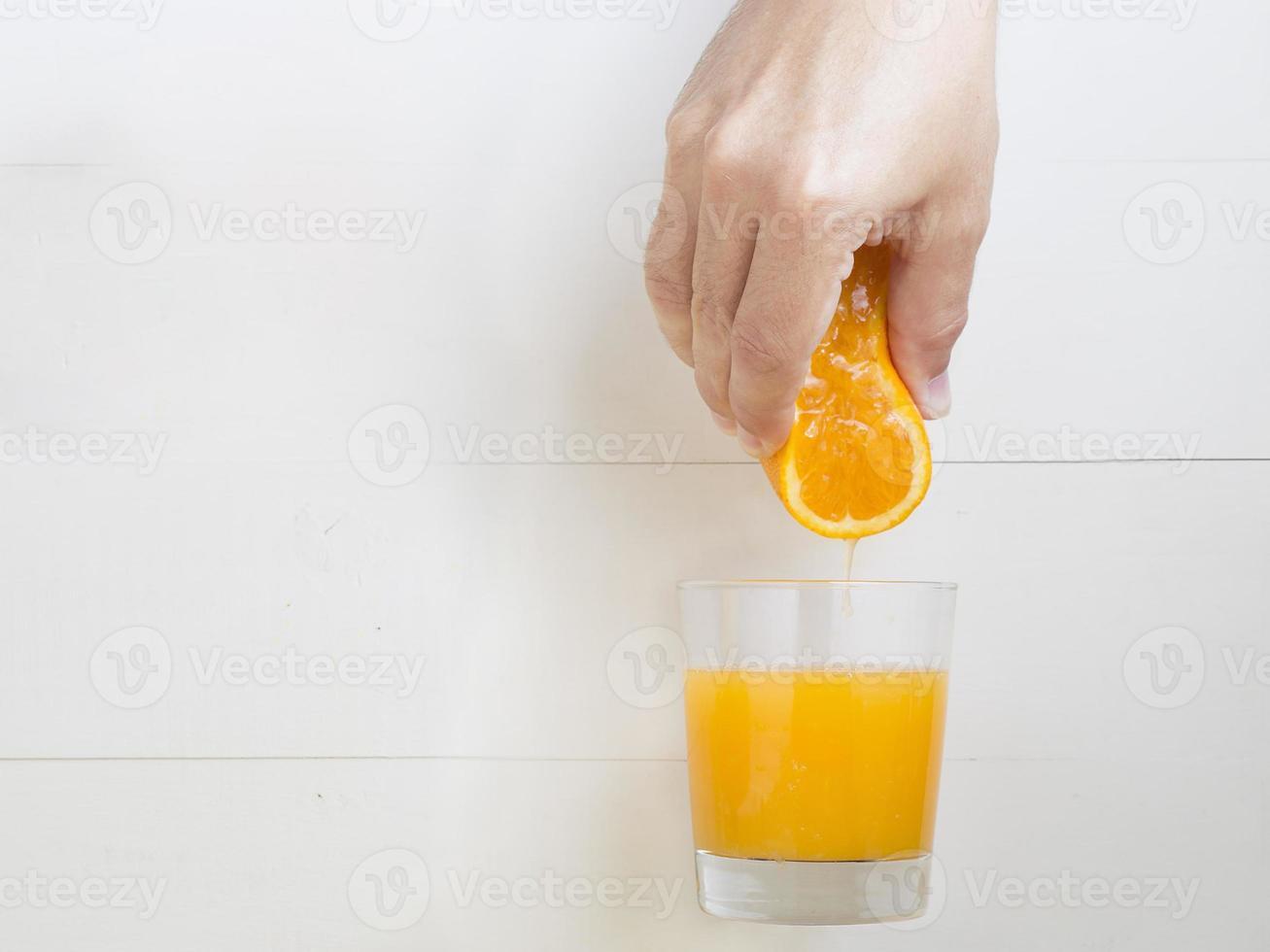 manhand som pressar apelsin på apelsinjuice foto