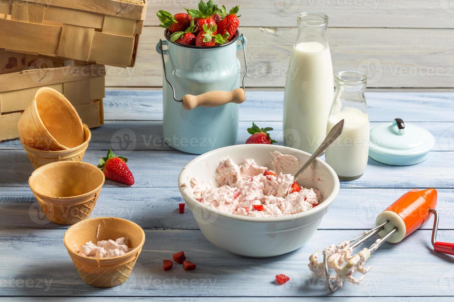 vispad grädde och färska jordgubbar som ingredienser för iskräm foto
