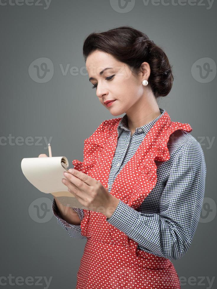 hemmafru som skriver ner receptingredienser foto