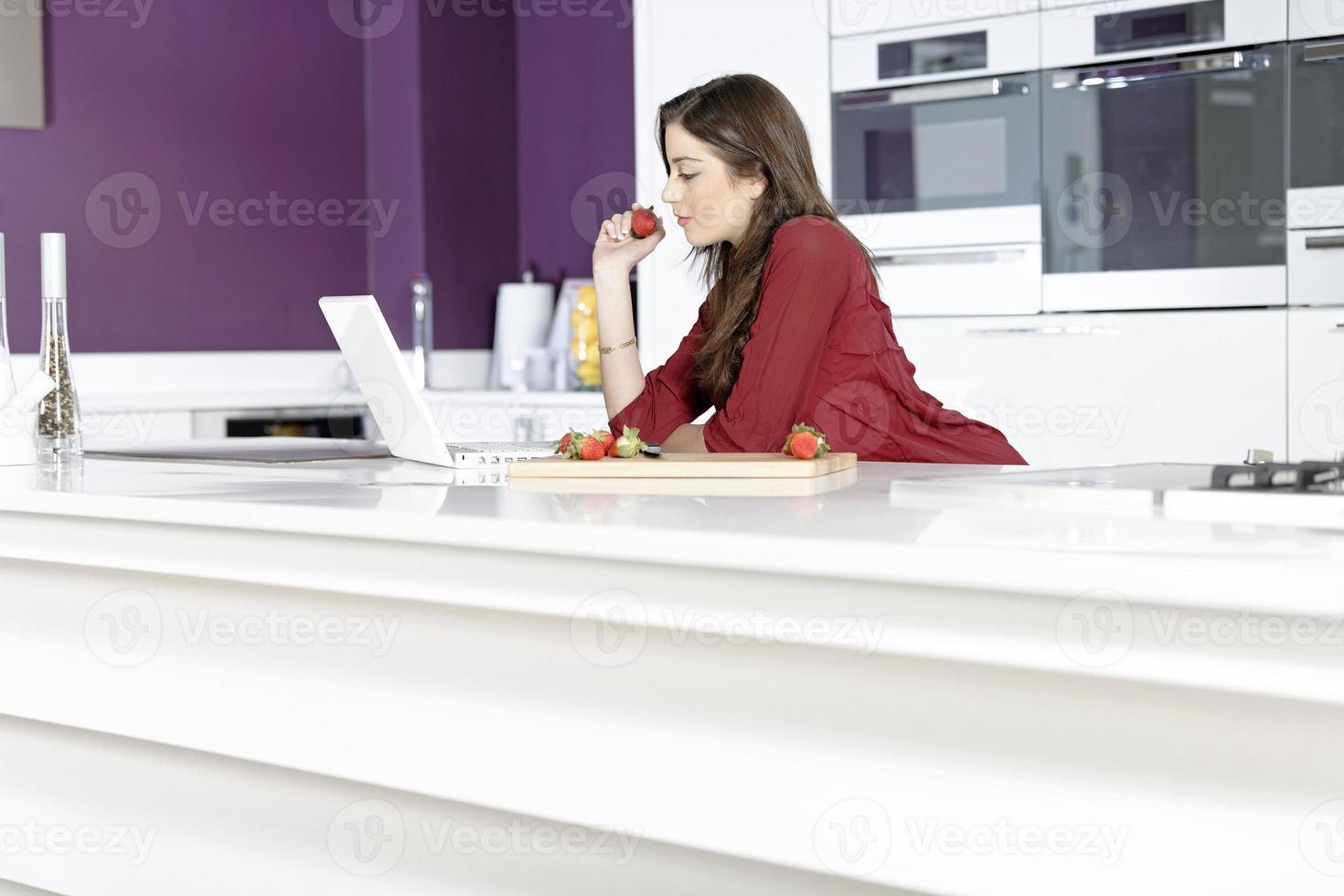 kvinna i köket läser recept foto