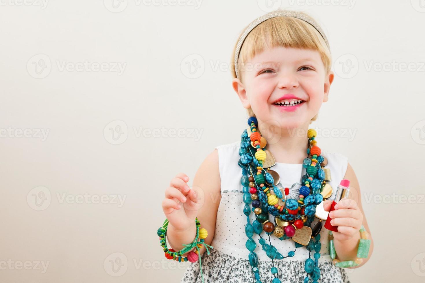 liten flicka med läppstift foto
