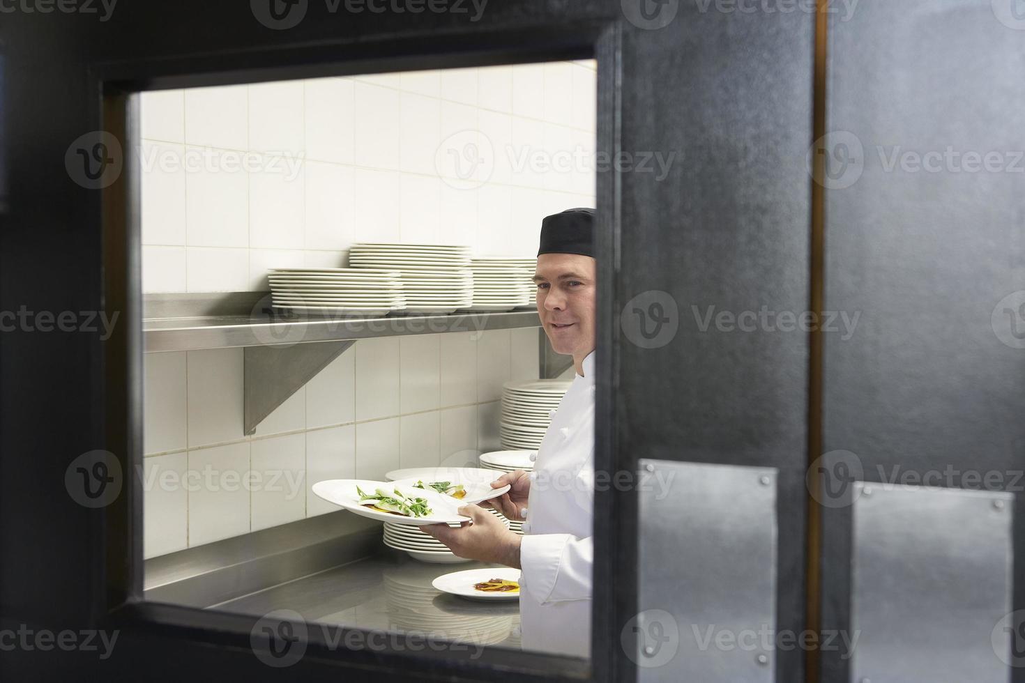 manlig kock med matplattor i köket foto