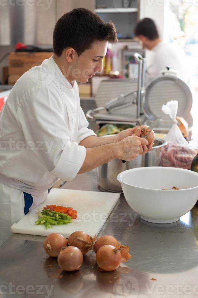 kock som skär grönsaker foto