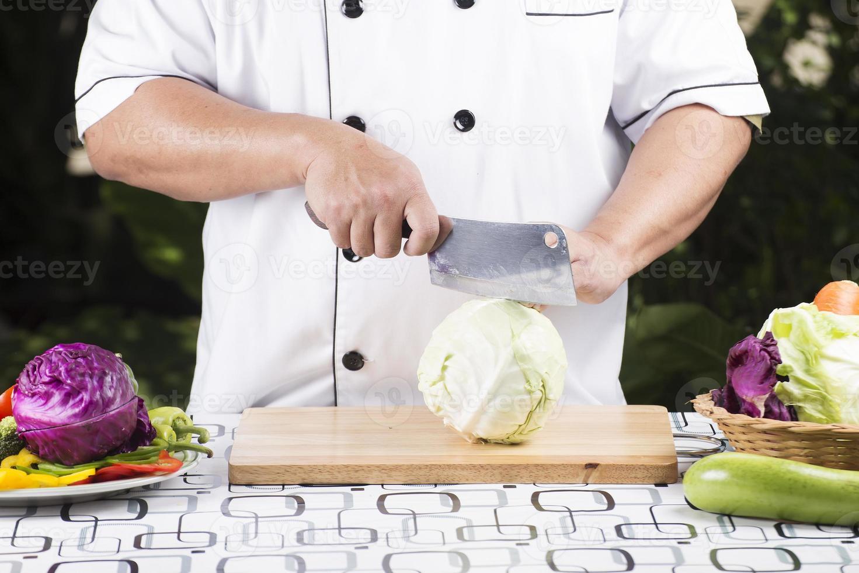 kock som skär kål foto