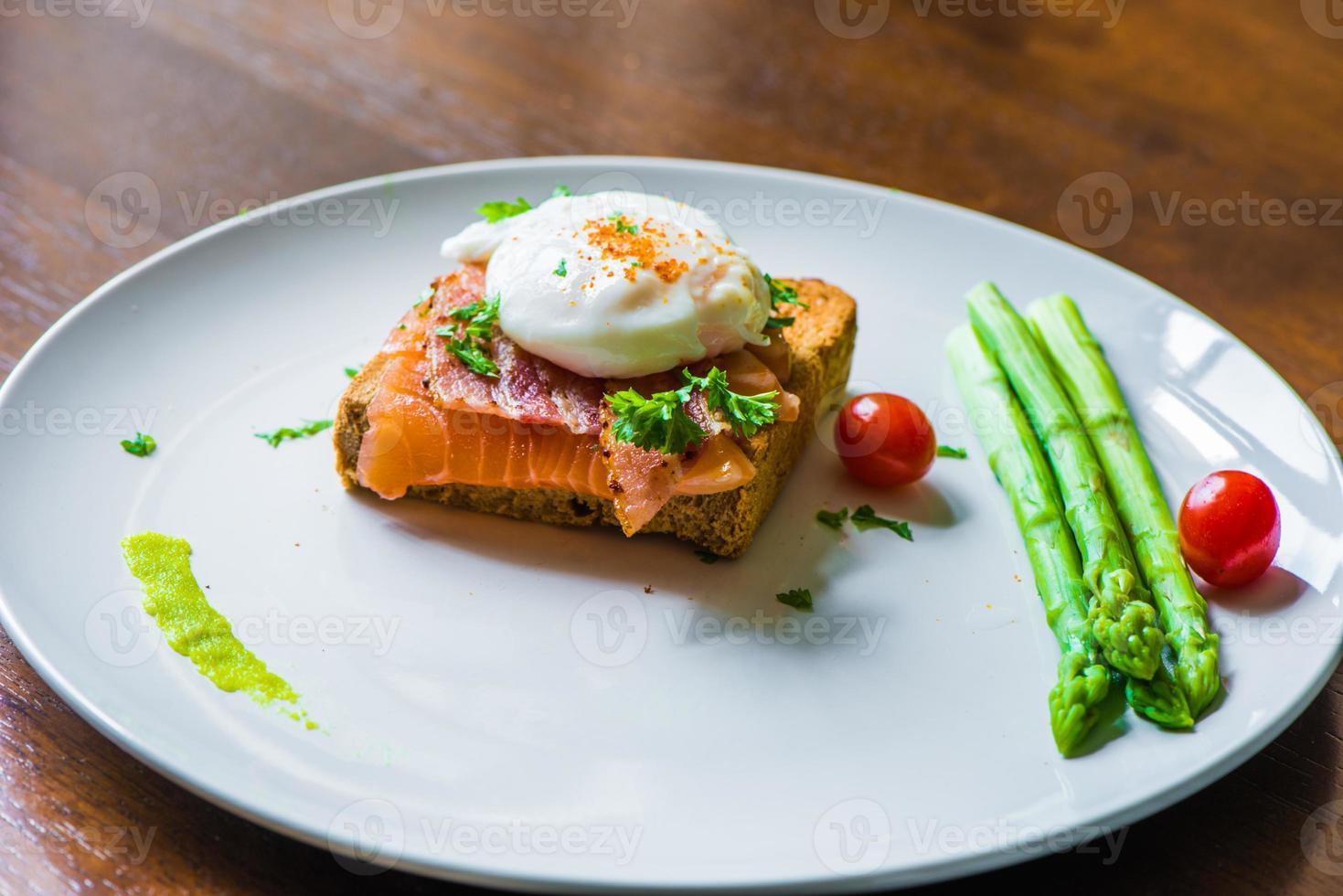 smörgås med pocherat ägg, parmaskinka och lax foto