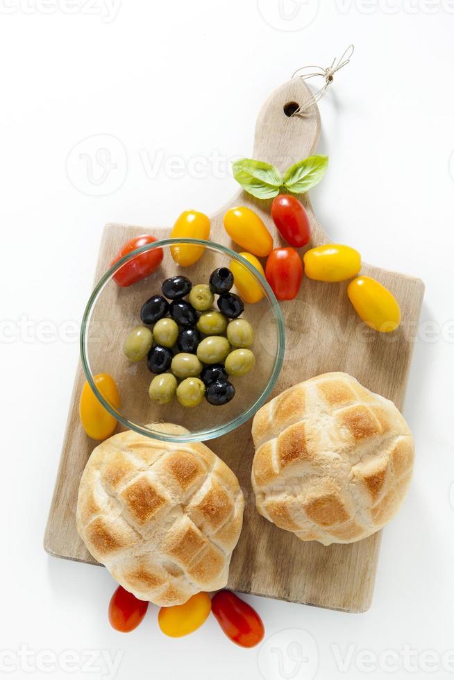 bröd, oliver, olika typer av tomat. på vitt. Ingredienser foto