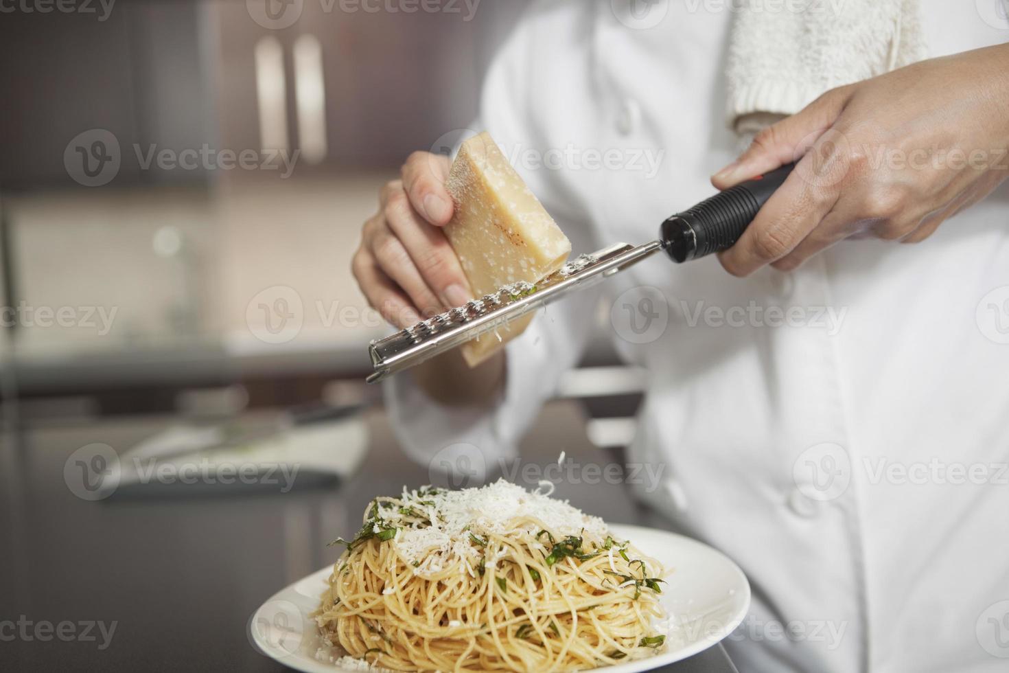 kock som galler ost på pasta i köket foto