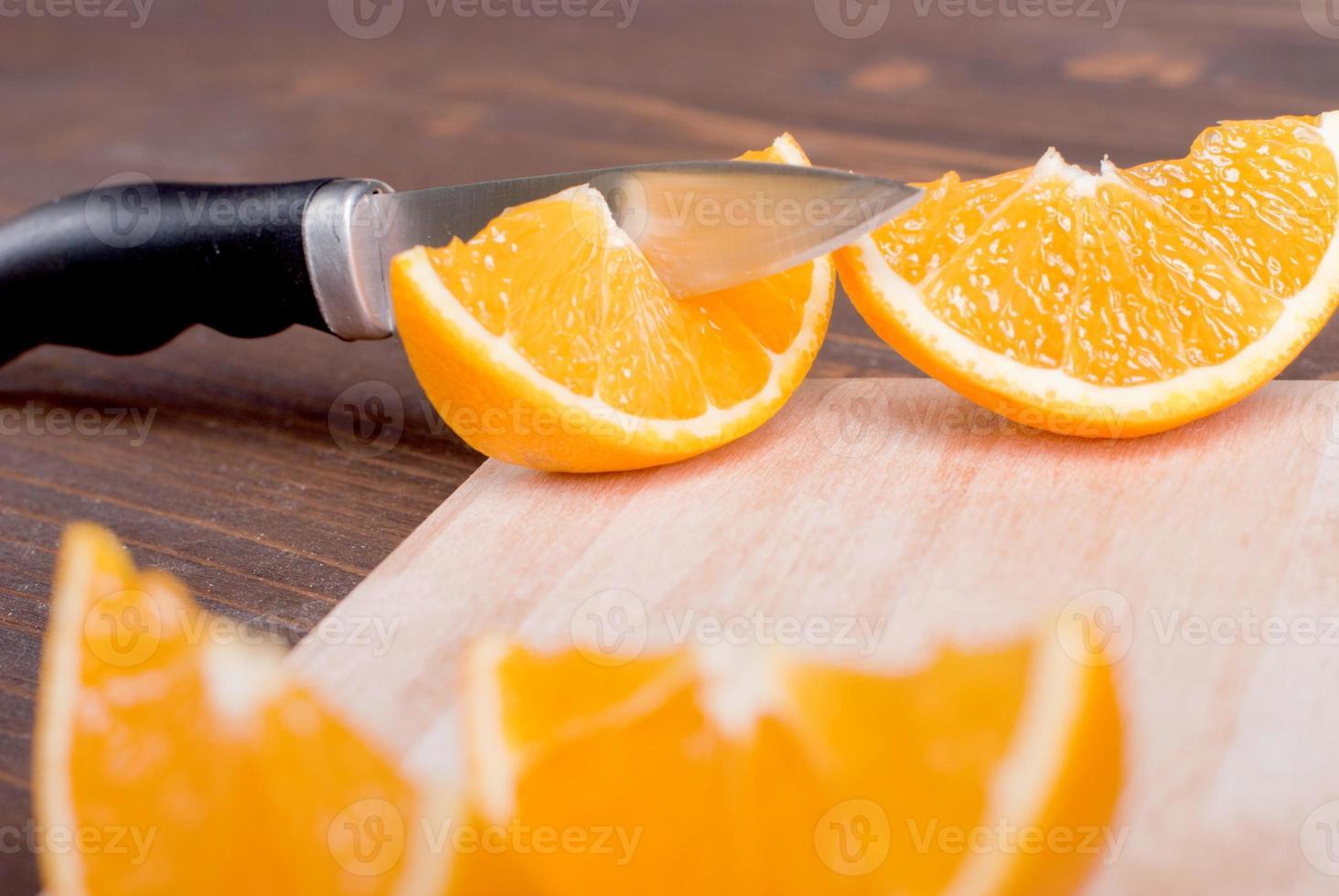 skivad mogen aptitretande läcker apelsin på skärbrädan bredvid foto