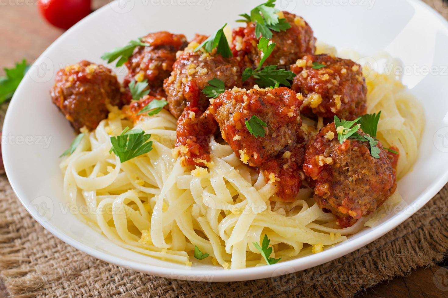 fettuccinapasta med köttbullar i tomatsås foto