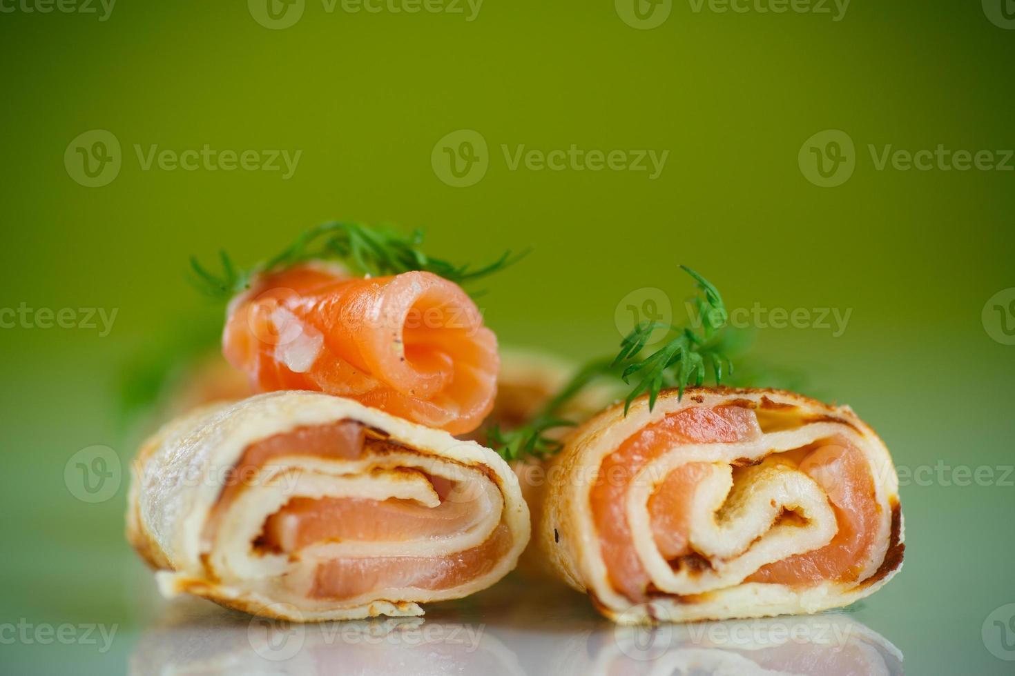 rullar av tunna pannkakor med saltad röd fisk foto