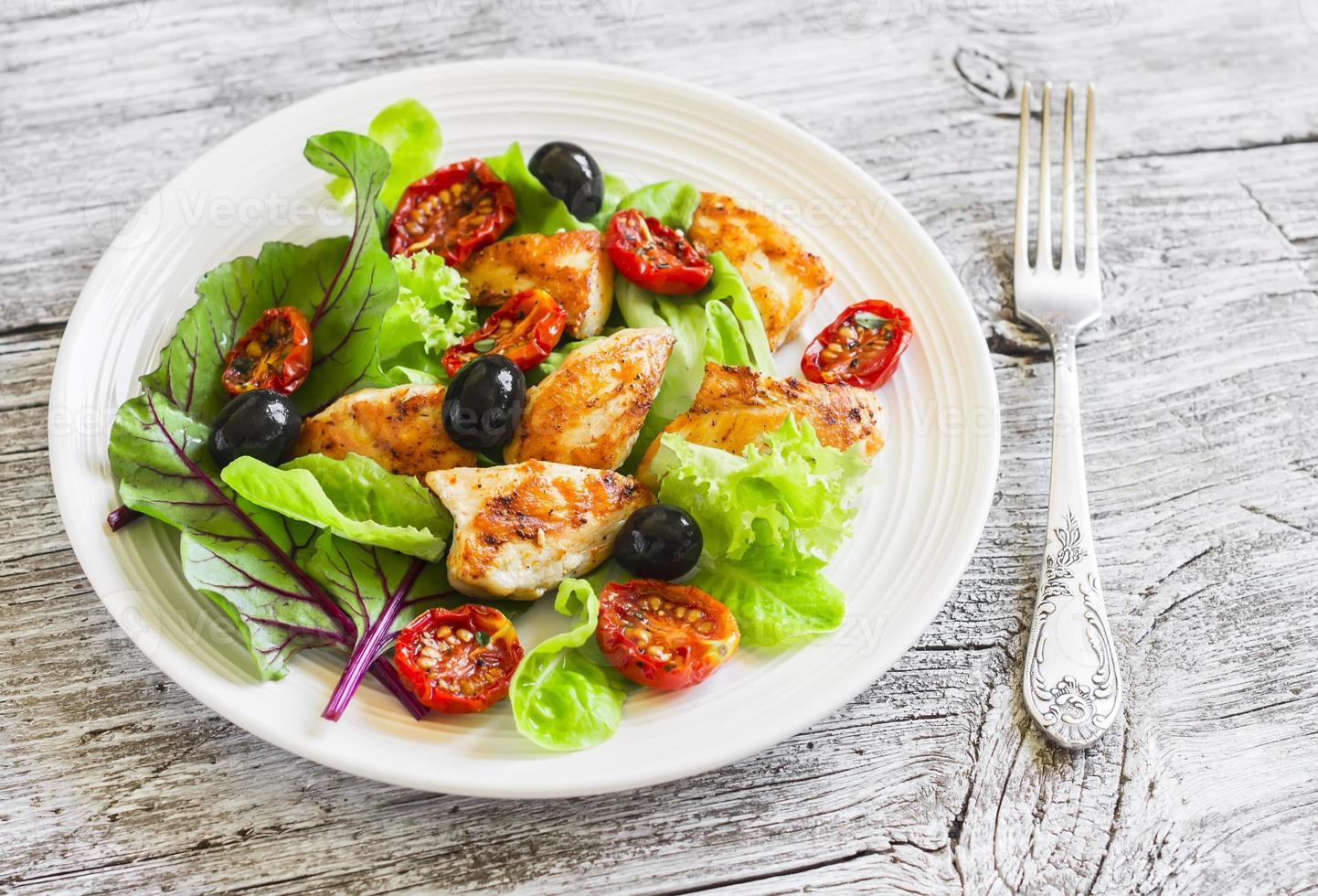 färsk sallad med kycklingbröst, soltorkade tomater, grön sallad foto