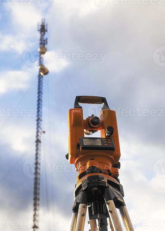 teodolit och telekommunikationstorn foto