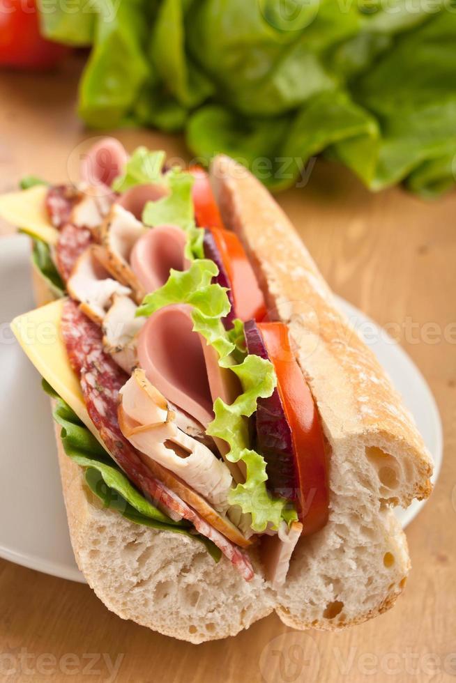 lång tunnelbagsbaguettsmörgås med kött, grönsaker och ost foto
