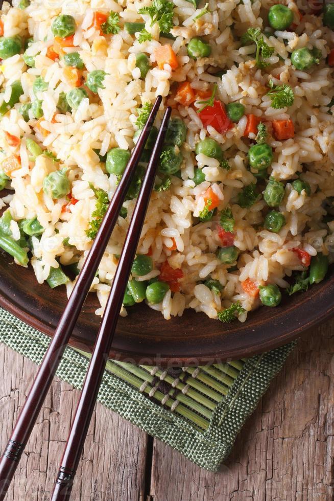 stekt ris med ägg, ärtor, morötter närbild vertikalt ovanifrån foto