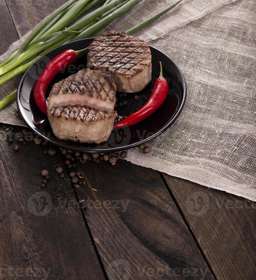 nötköttbiff med på ett träbord foto