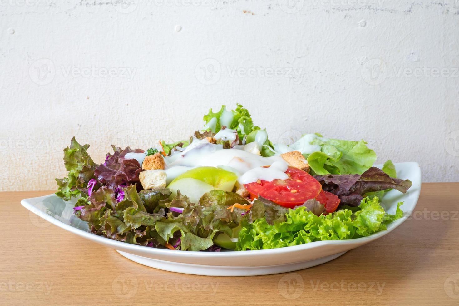 färsk blandad grönsaksallad, salladdressing. foto