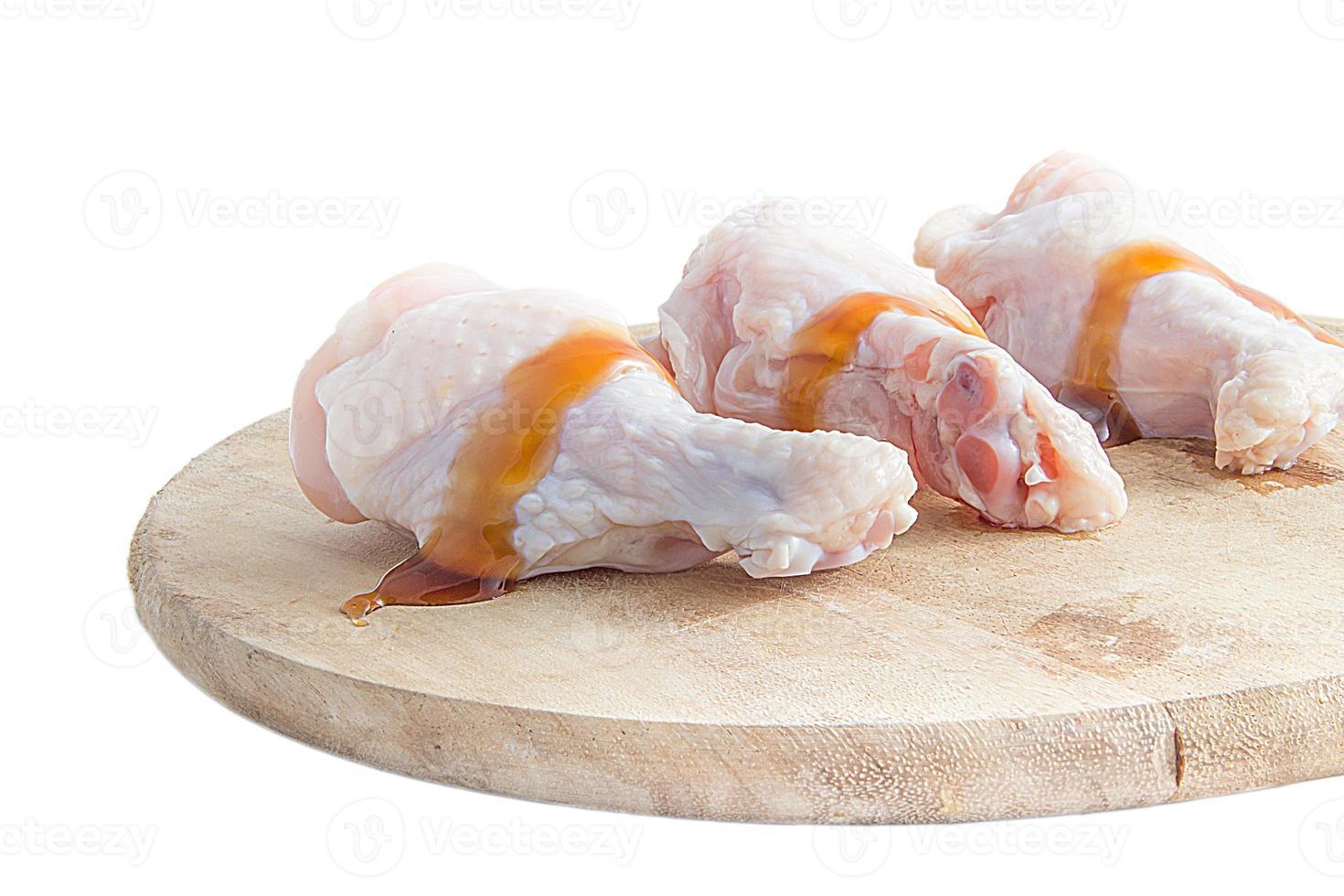 rå kycklingben på träskärbrädor på vit bakgrund foto
