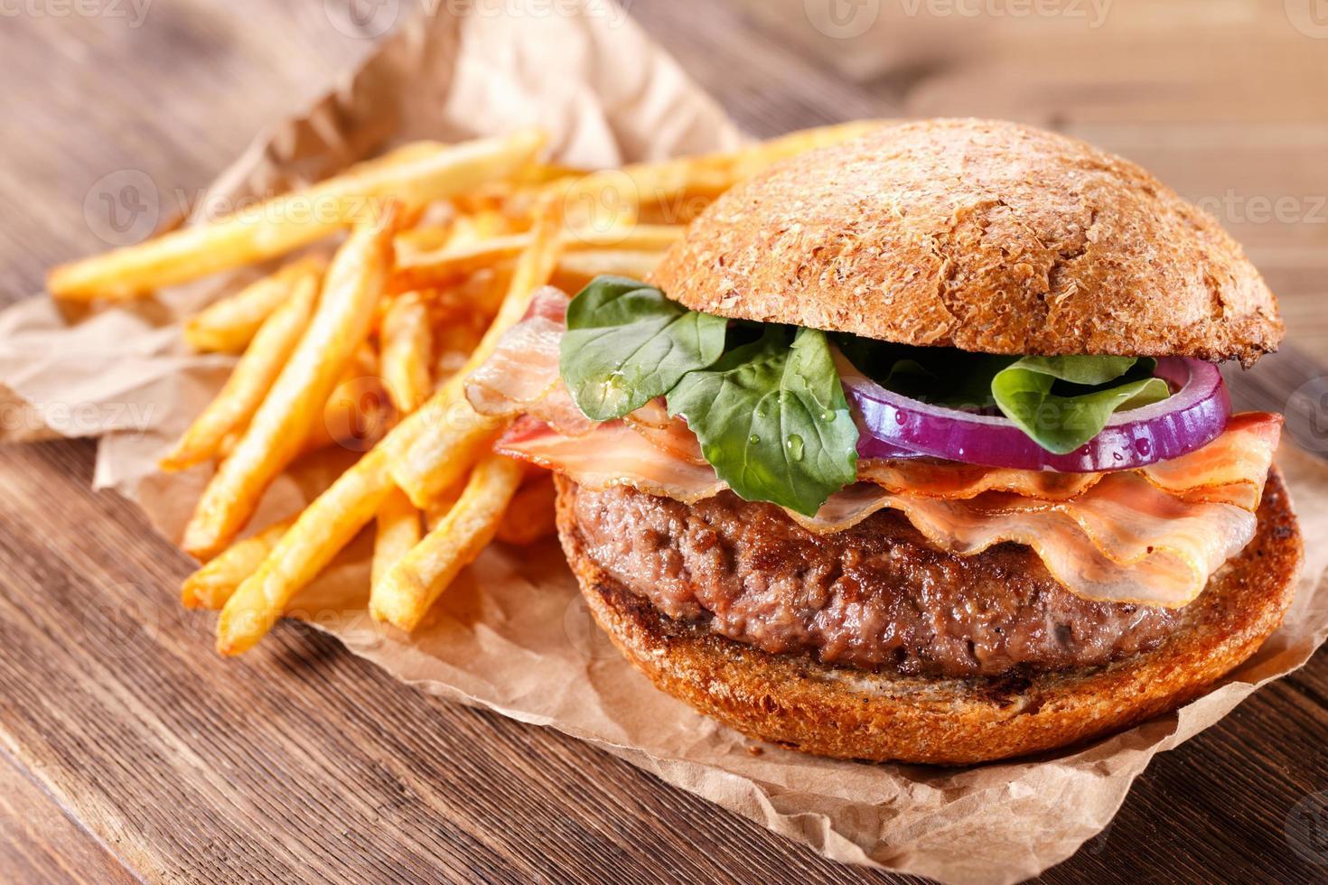 hamburgare och pommes frites på nära håll på träbakgrund. foto