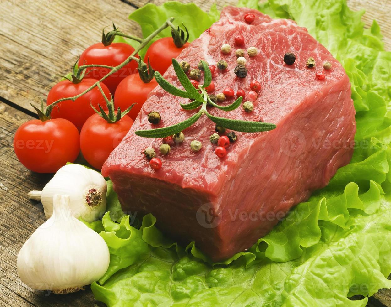 rå biff med grön sallad på träplatta foto
