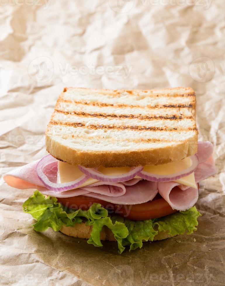 toast skinkasmörgås på brunt papper foto