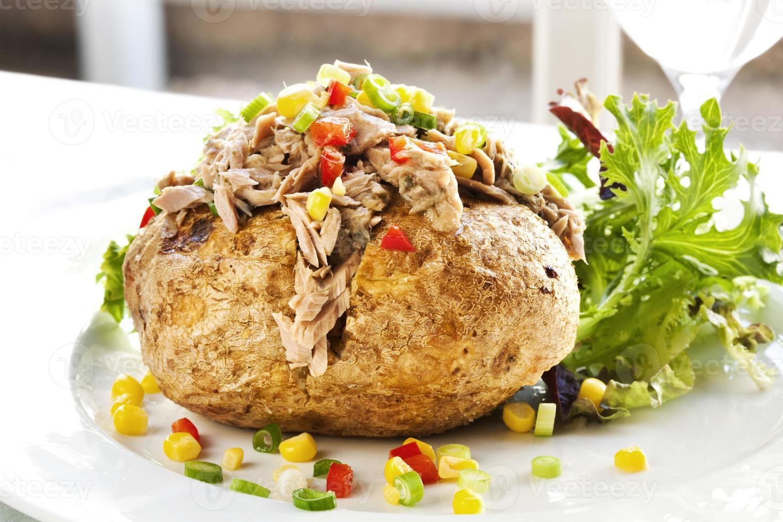 servering av bakad potatis med tonfisk och grönsaksfyllning foto