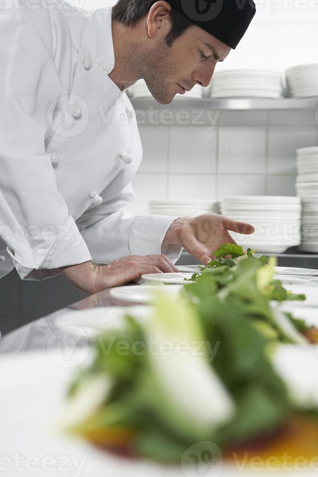 manlig kock som förbereder sallad i köket foto