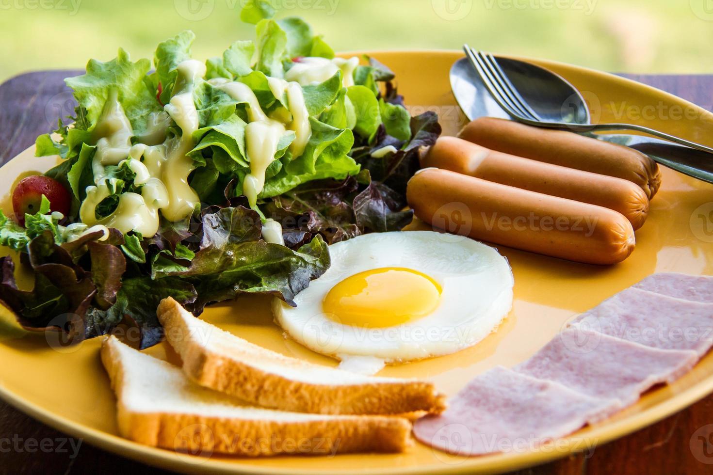 Frukosten består av ägg, sallad, bröd, bacon och korv foto