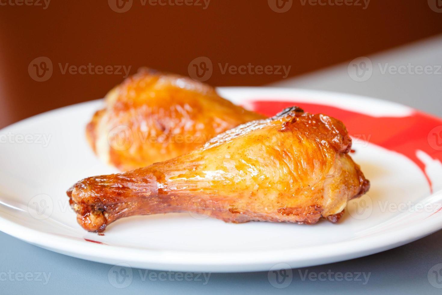 rostade kycklingtrumpinnar på vit platta foto