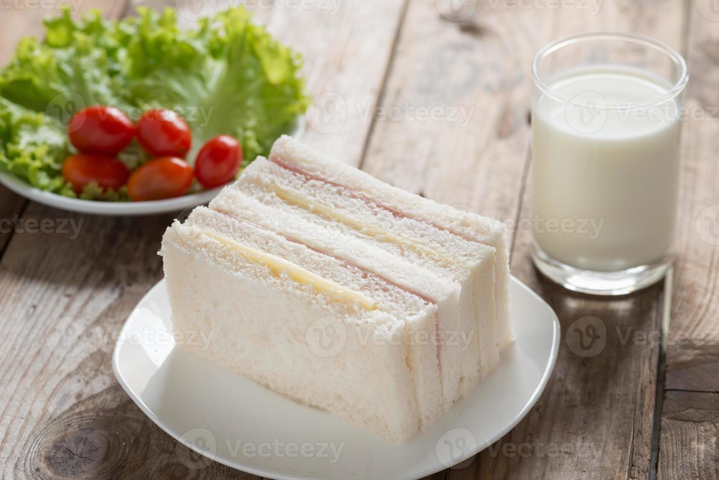 smörgås, skinka med ost och mjölk på träbord. foto