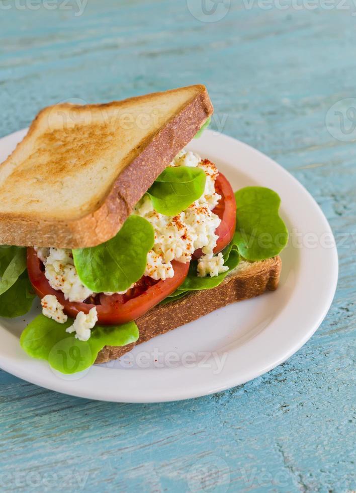 smörgås med ägg, tomat och sallad på en vit platta foto
