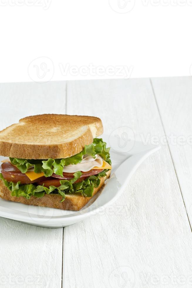 skinkasmörgås med rostat bröd på den vita plattan foto
