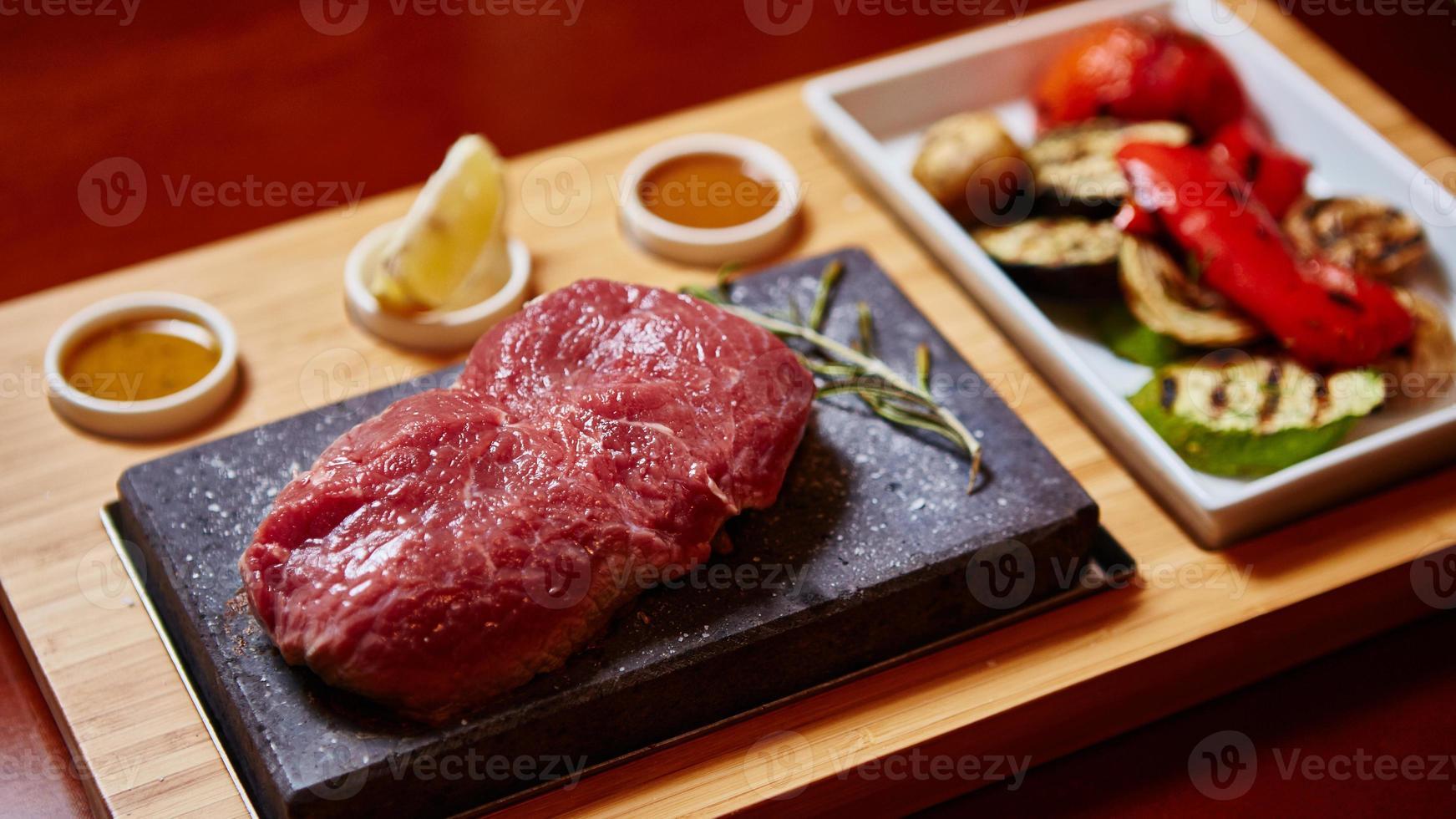kött grillad på sten med grönsaker foto