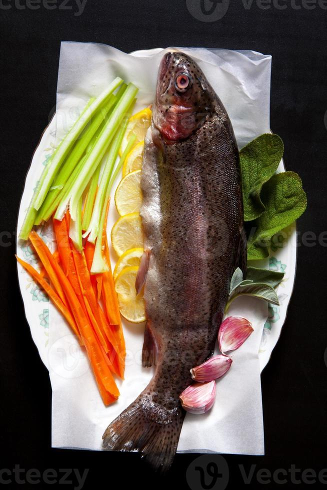 rå färsk fisk med grönsaker och kryddor. morötter foto