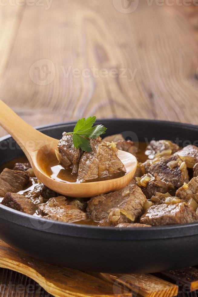 nötköttgryta - träbakgrund foto