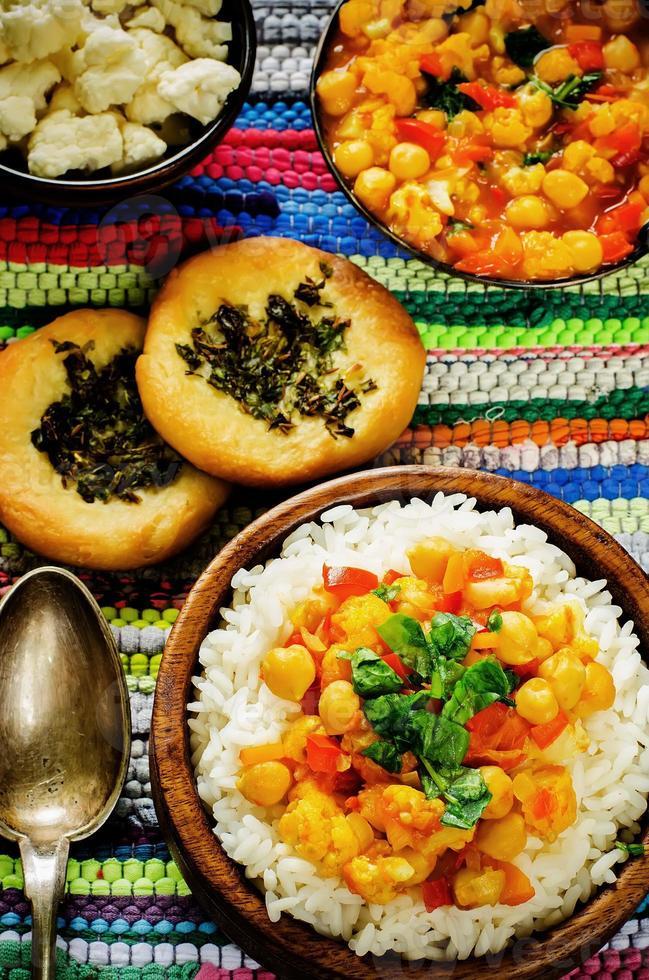 ris med curry kikärter med grönsaker och arabiskt plattbröd med örter foto