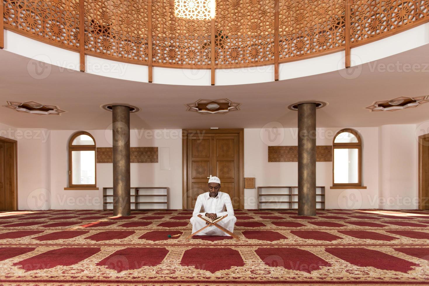 afrikansk muslim man läser koranen foto