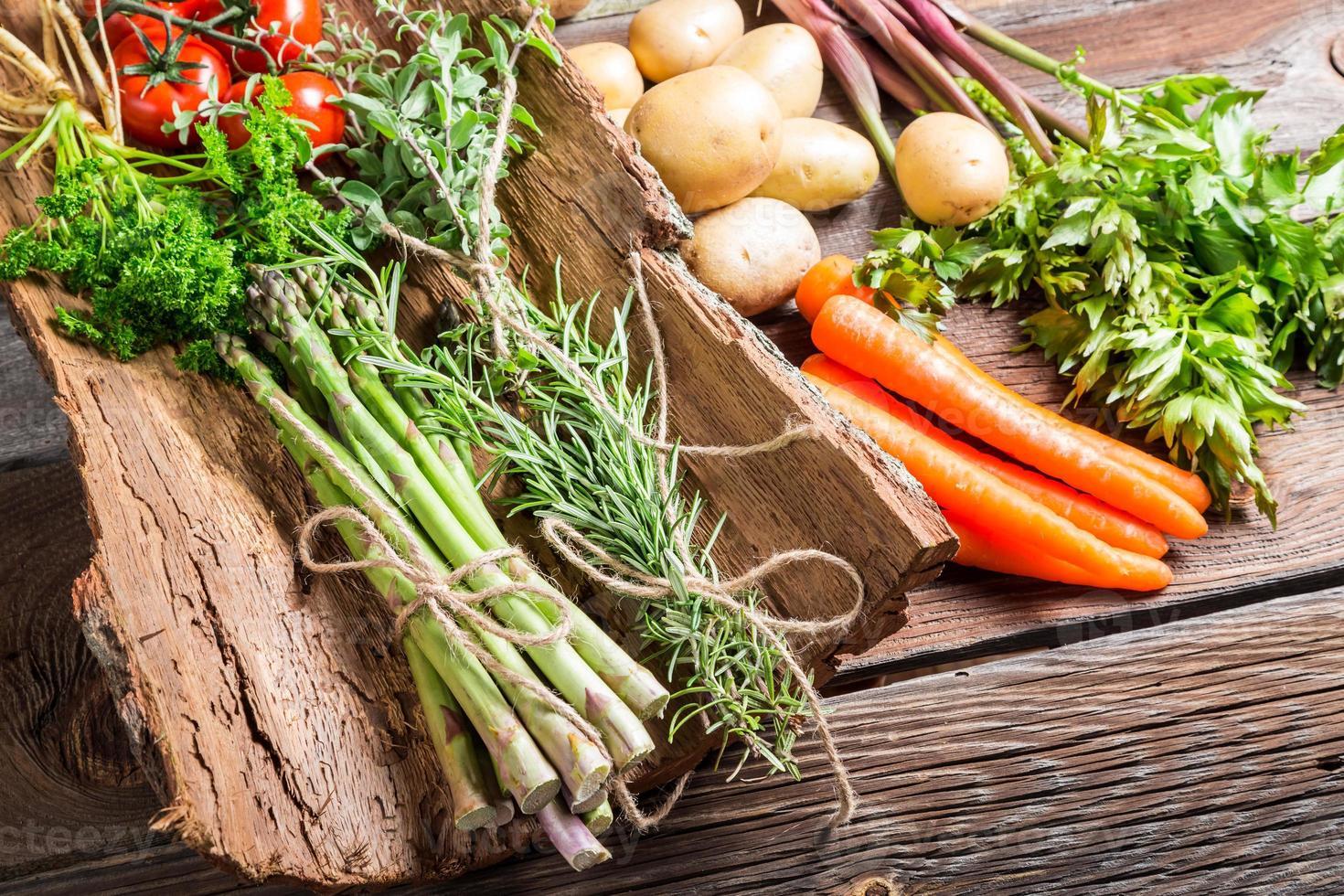 färska olika grönsaker på bark foto
