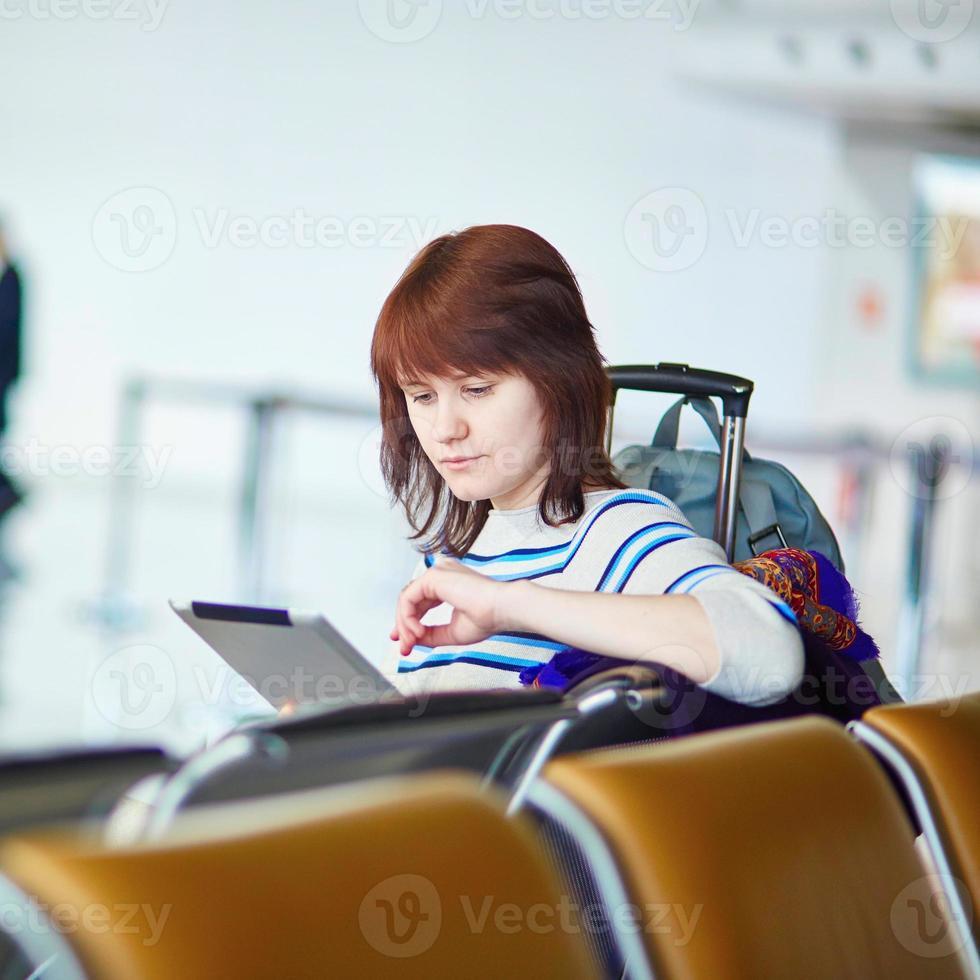 ung passagerare på flygplatsen med sin surfplatta foto