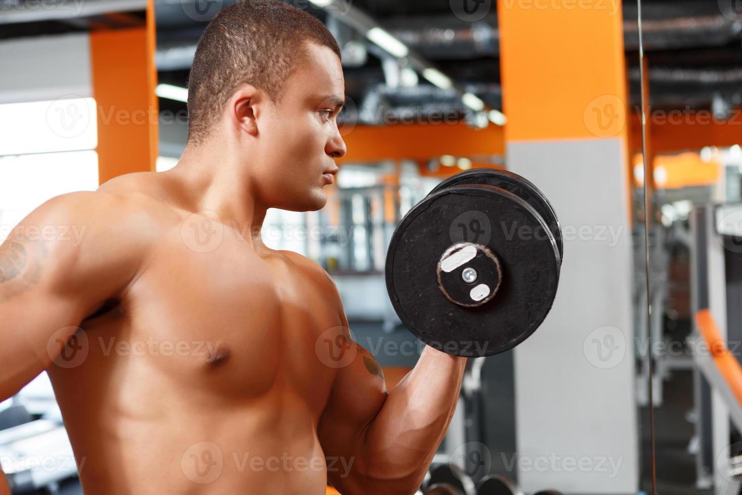 bild av man lyfter vikt i gymmet foto
