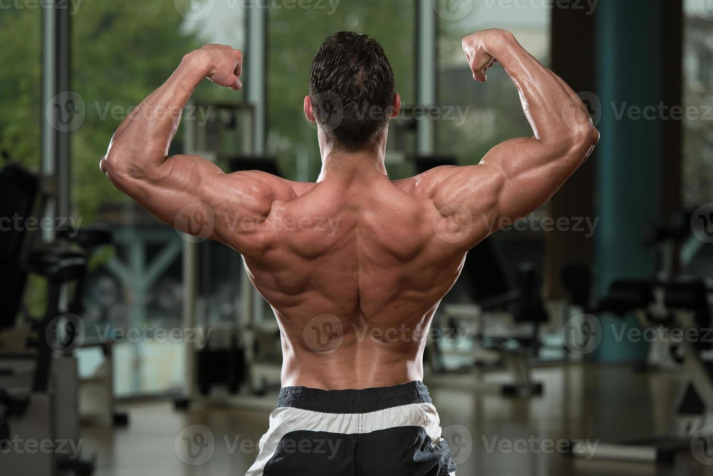 kroppsbyggare utför bakre dubbla biceps pose foto
