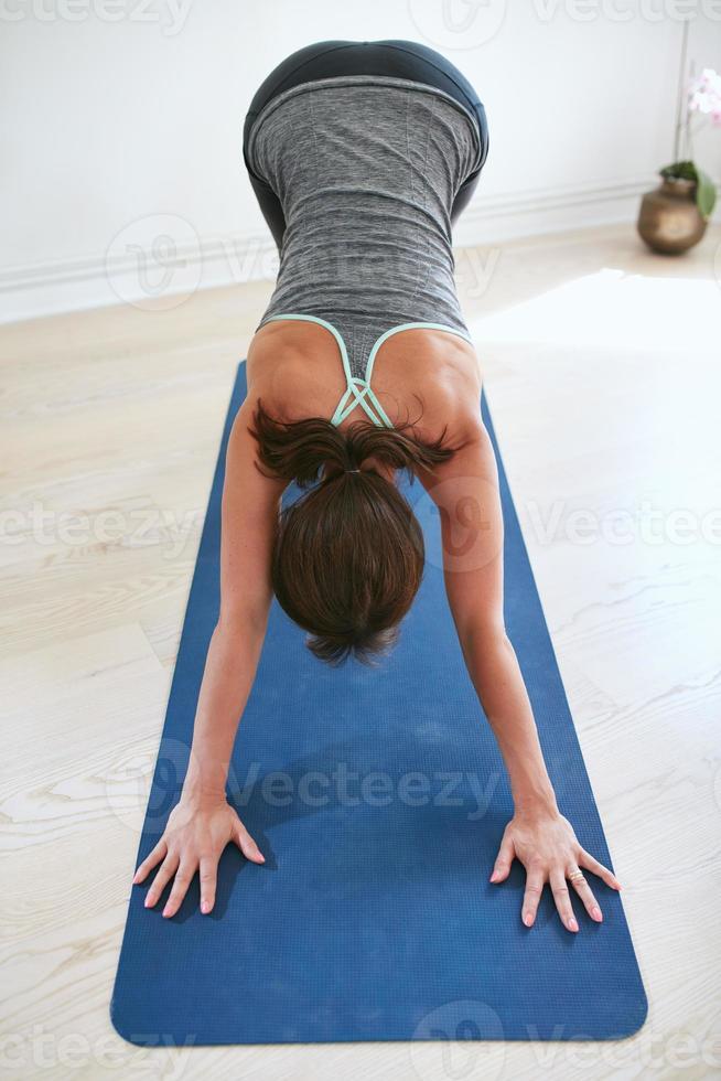 kvinna som gör yoga framåt böj poserar på gymmet. foto