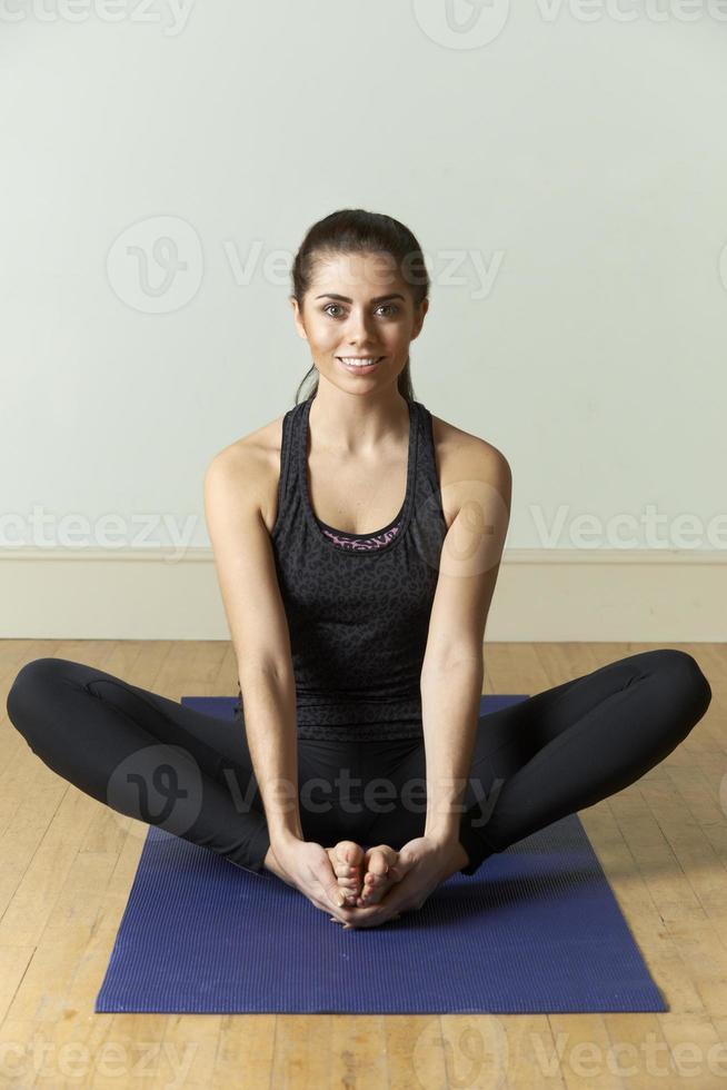 ung kvinna i sportkläder som tränar på matta foto