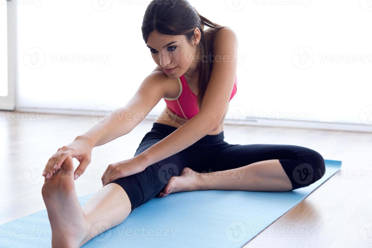 vacker frisk ung kvinna som gör träning hemma. foto