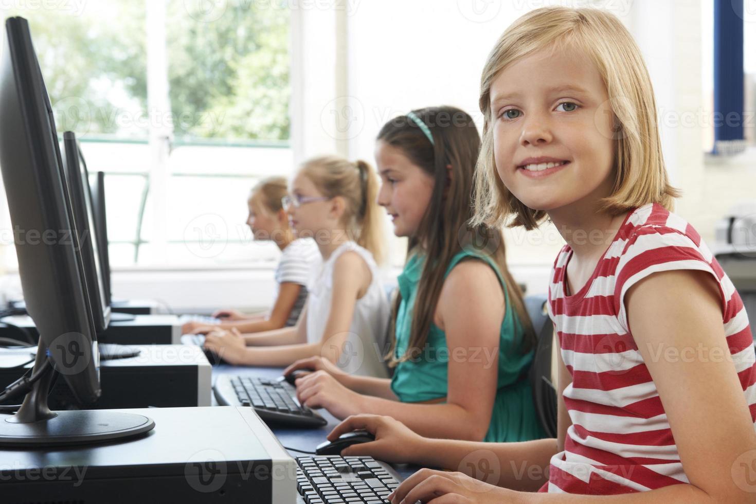 grupp kvinnliga grundskolebarn i datorklass foto