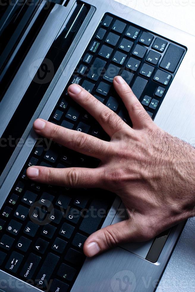 hand på den bärbara datorn foto