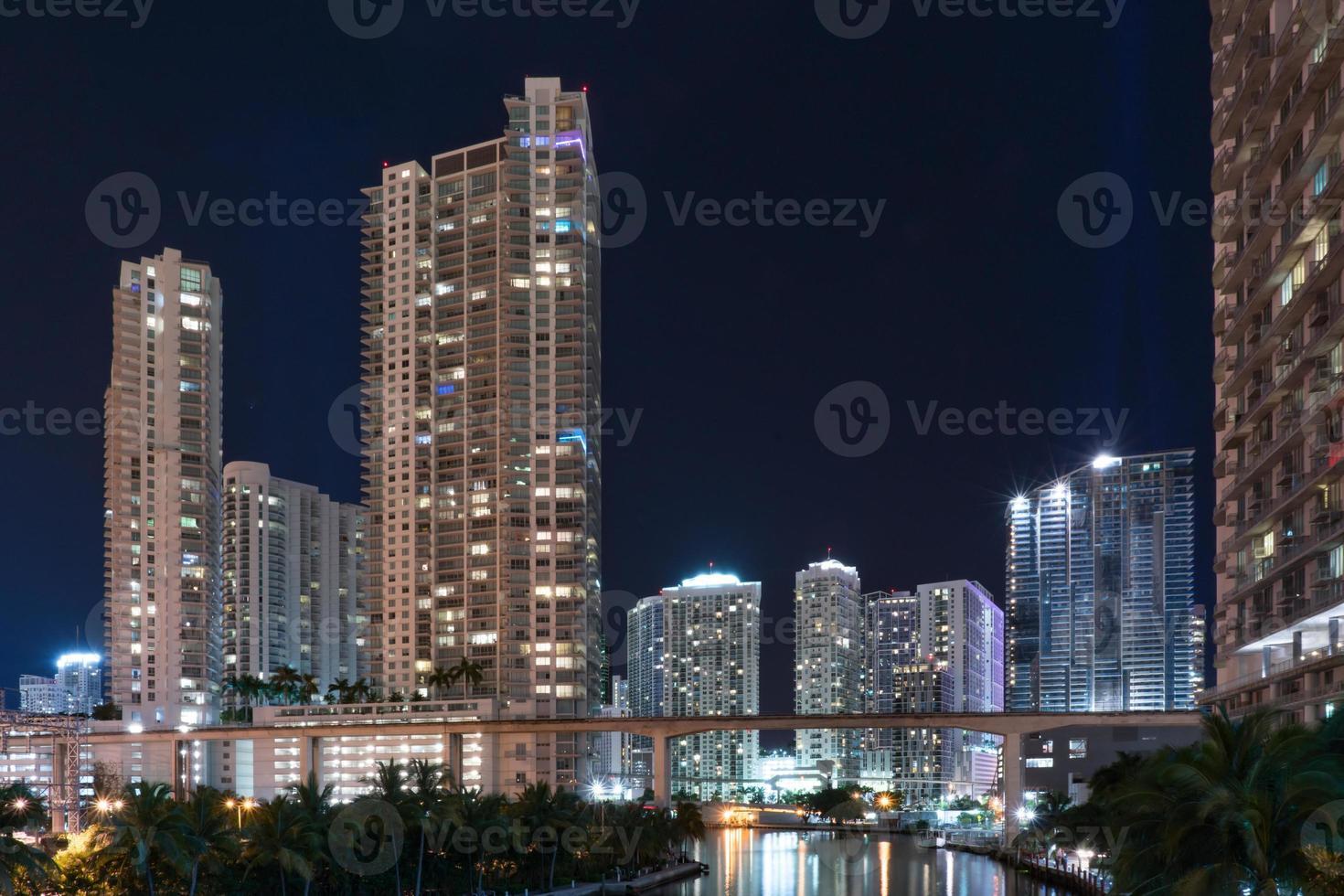miami skyline på natten längs miami floden foto